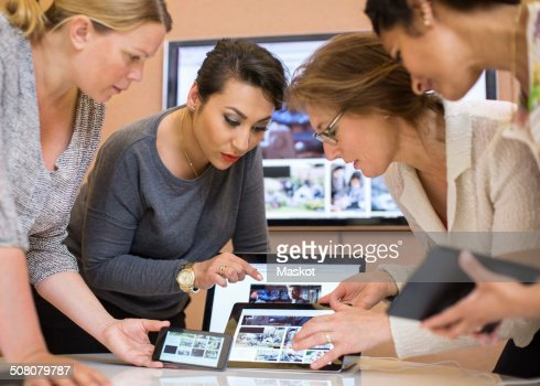 Female Photo Editors Discussing Over Digital Tablet In ...