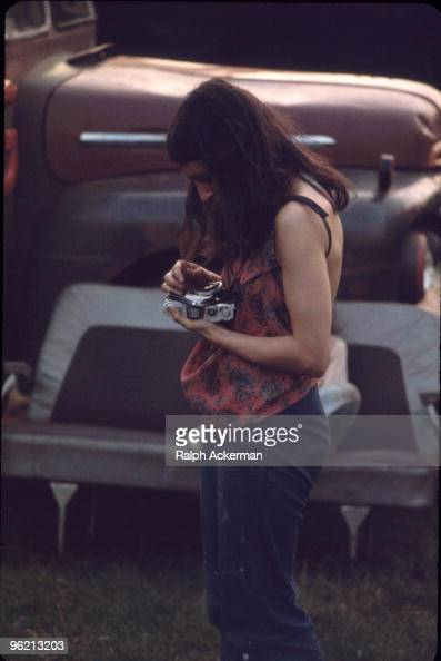 A female photographer changes the lens on her camera during the Woodstock Music and Arts Fair Bethel New York August 1969 The festival ran from...