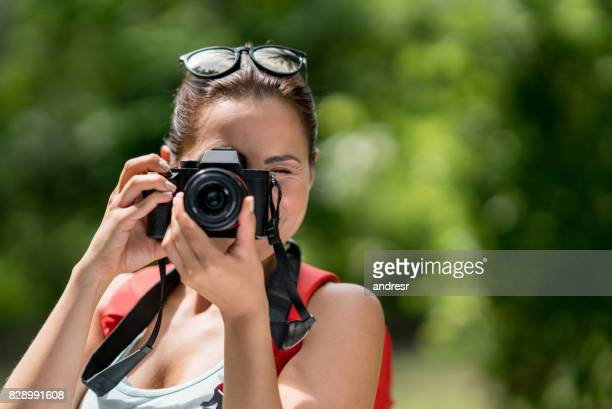 Female photographer hiking and holding the camera outdoors