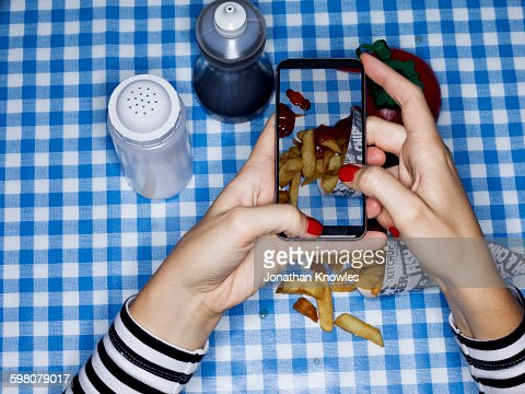 Female photographing chips on table