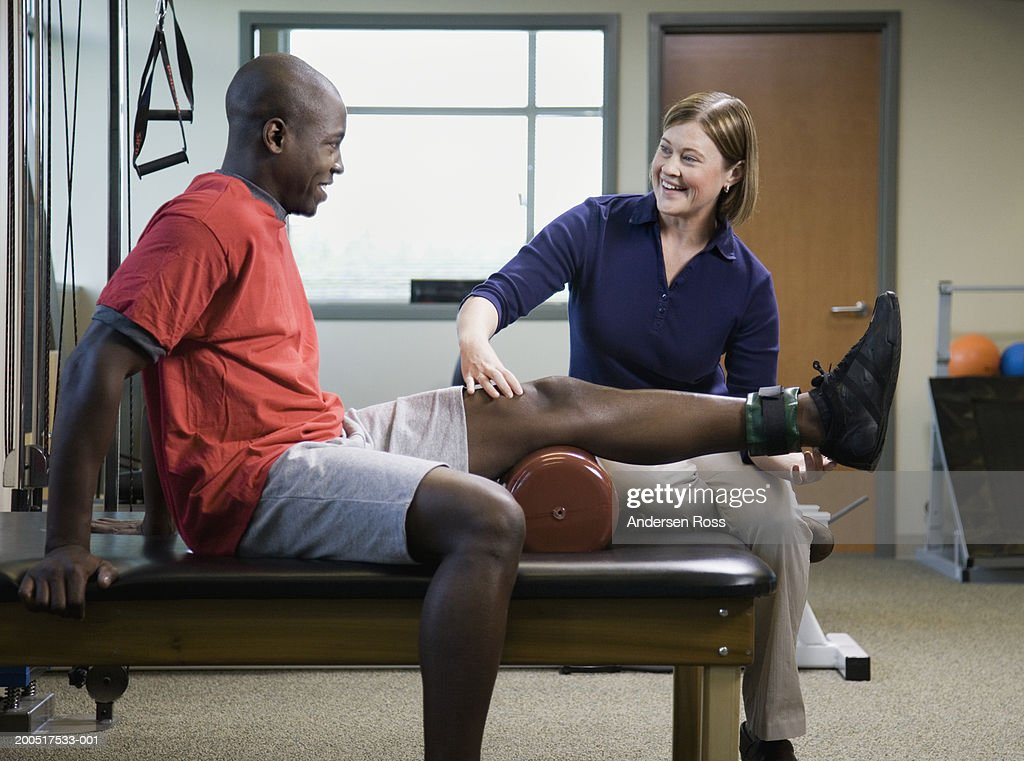 Female physical therapist assisting man with leg exercise : Stock Photo