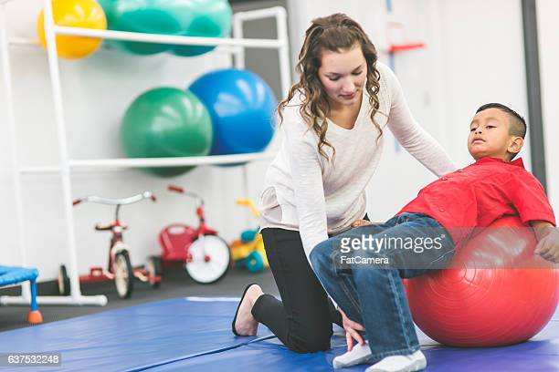 A female physical therapist doing rehabilitation with a child patient