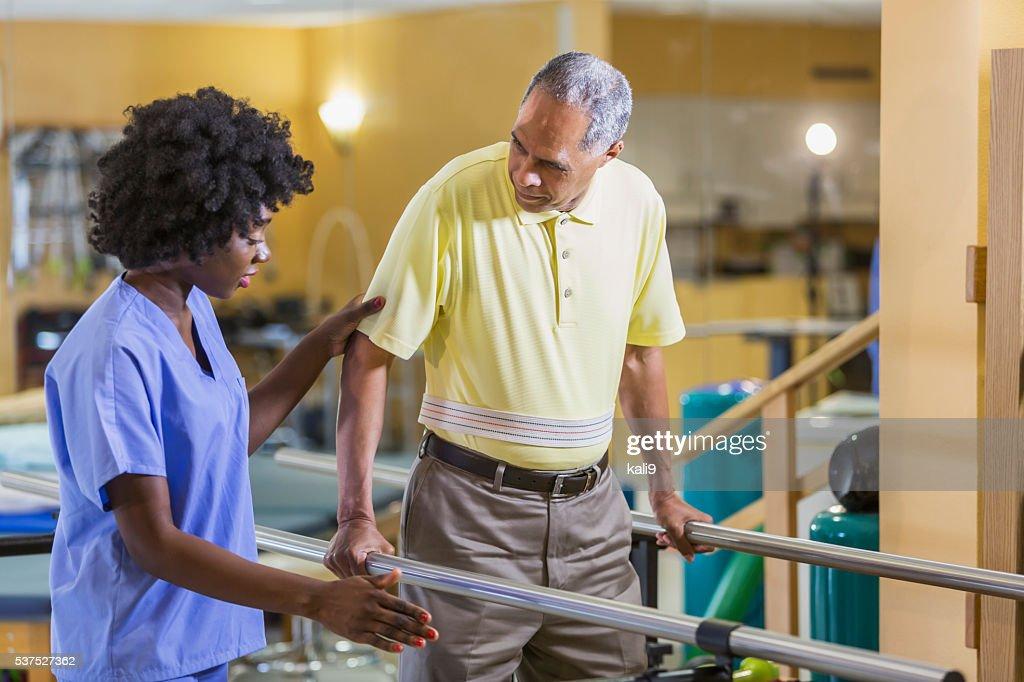 Femmina fisioterapista, lavorando con paziente maschio : Foto stock