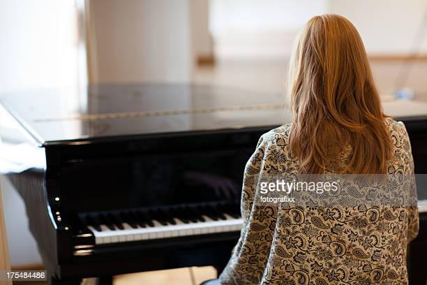 Femme pianiste jouer dans un grand piano, vue arrière noir