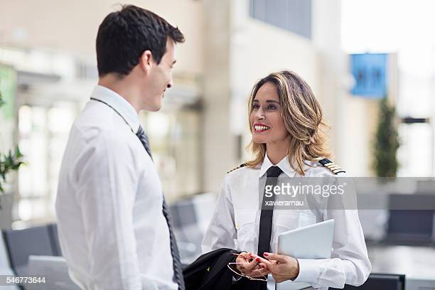 Female pilot and flight attendant man talking in the airport