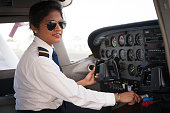 A female pilot at the controls of a Cessna aircraft. She is dressed in her pilots uniform.