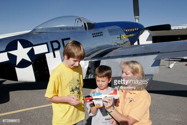 A female pilot talking to two boys next to a 1945 P51D Mustang at the Indiana Aviation Museum