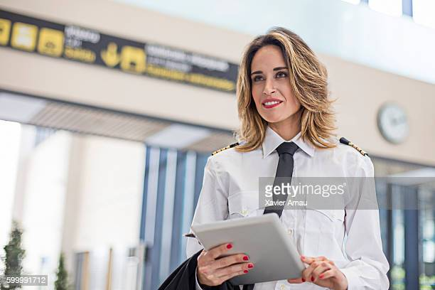 Female pilot using digital tablet in the airport