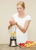 female placing ingredients into blender
