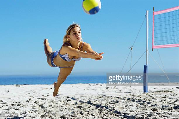 Female playing beach volleyball, diving to catch ball
