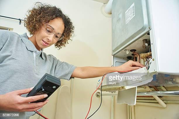 Femme plombier électriquement tests d'un chauffe-eau