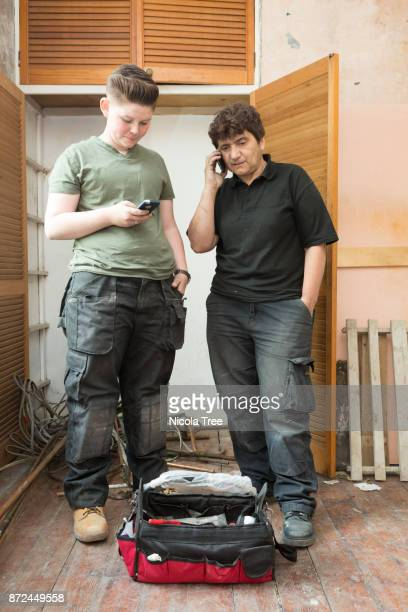 female plumber on the phone and her apprentice standing next to her, with a tool box at their feet.