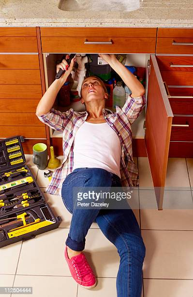 Female plumber under kitchen sink
