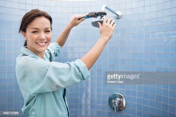Weibliche Klempner Arbeiten an Duschkopf im Badezimmer