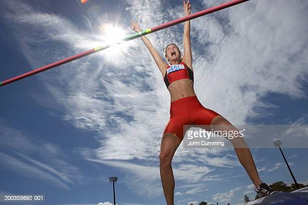 Female pole vaulter landing on mat, arms raised, shouting
