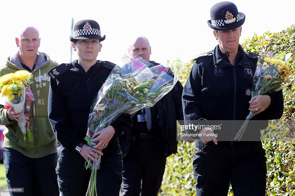 Female police constables pay their respects and place floral tributes near to the scene in memory of WPC's Nicola Hughes and Fiona Bone in Hattersley on September 19, 2012 in Manchester, England. Local man Dale Cregan, 29, has been arrested in connection with the shooting of WPC's Nicola Hughes and Fiona Bone, who were killed as they responded to a routine incident at Abbey Gardens in Hattersley shortly before 11am yesterday.