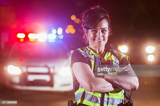 Female police officer at night, lights on patrol car