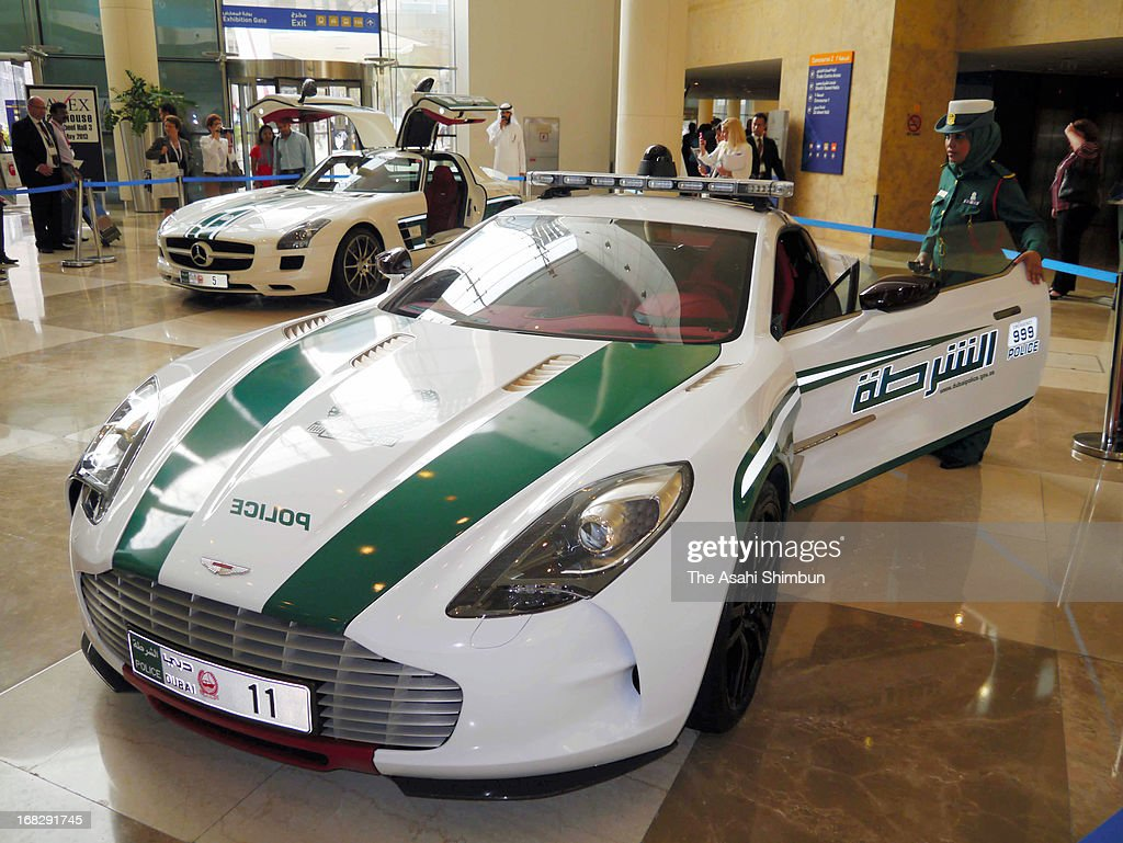 A female police officer checks Aston Martin 'One-77' patrol car on May 6, 2013 in Dubai, United Arab Emirates. Dubai Police has already launched Aventador of Lamborghini as patrol car, as well as General Motors' Chevrolet Camaro, Mercedes-Benz SLS AMG and Bentley's Continental GT.
