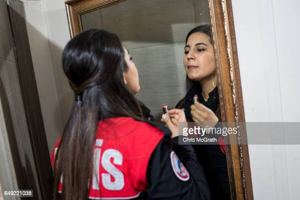 A female police officer from Istanbul's Motorcycled Police Unit puts on lipstick before heading out on patrol on March 7 2017 in Istanbul Turkey The...