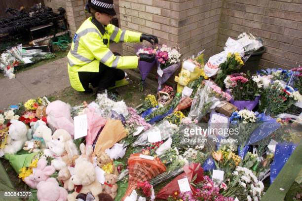A female police officer places flowers outside the home of Tracey Gallagher in Bournemouth after three of her four children died in a fire which...