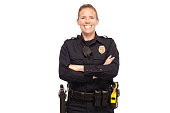 Happy female police officer posing with arms crossed against white background