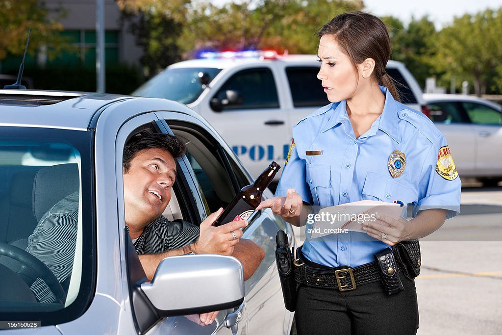 Female Police Officer Writing Citation for DUI : Stock Photo