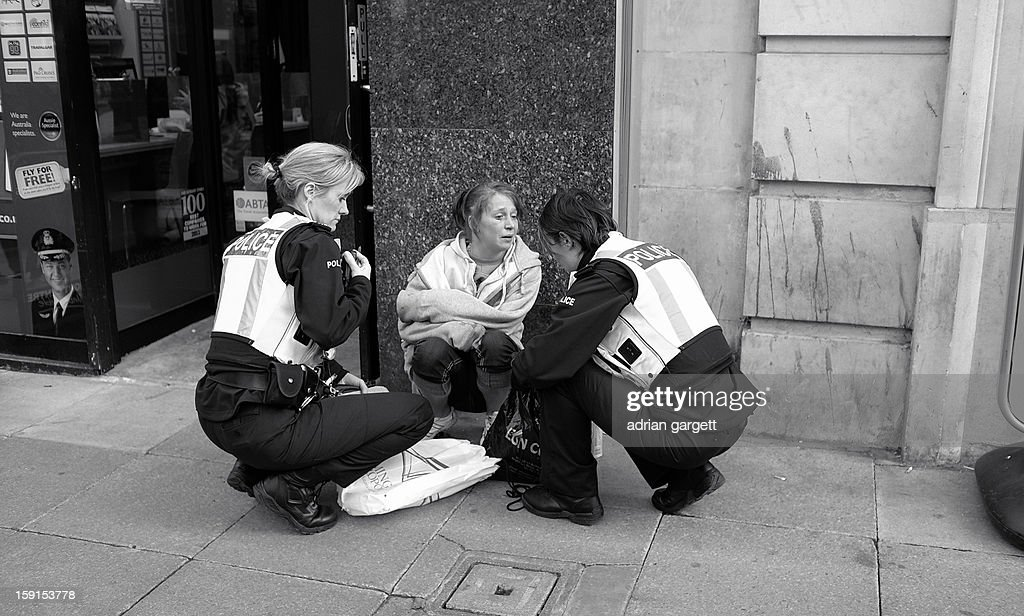 CONTENT] Female Police Officers. City Centre Law and Order. Police Officers searching the bag of a young woman. Officers question Female. City Centre Birmingham.