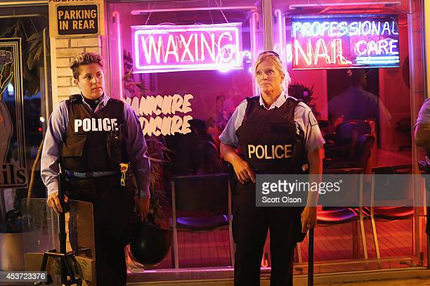 Female police officers stand guard before the mandatory midnight curfew on August 16 2014 in Ferguson Missouri The curfew was imposed on Saturday in...
