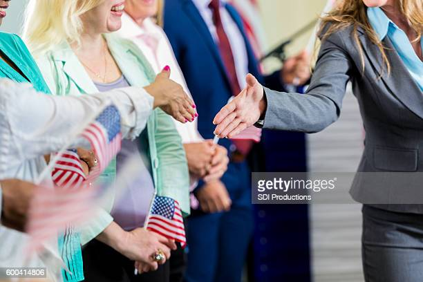 Female politician shaking hands with supporters at event