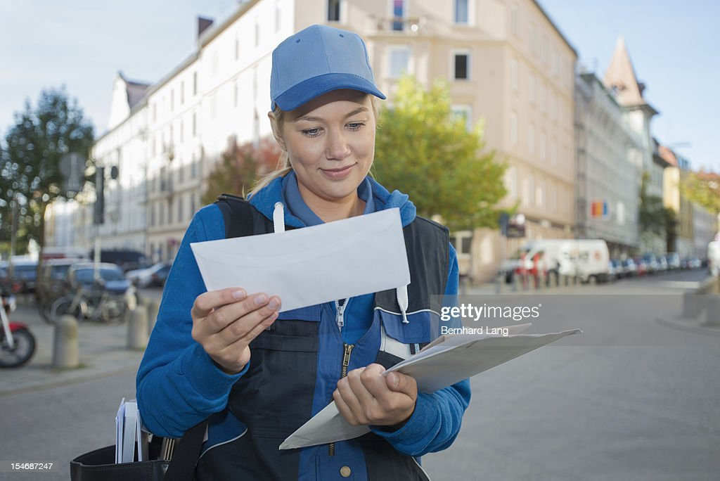 Female postal worker looking through mail : Stock Photo