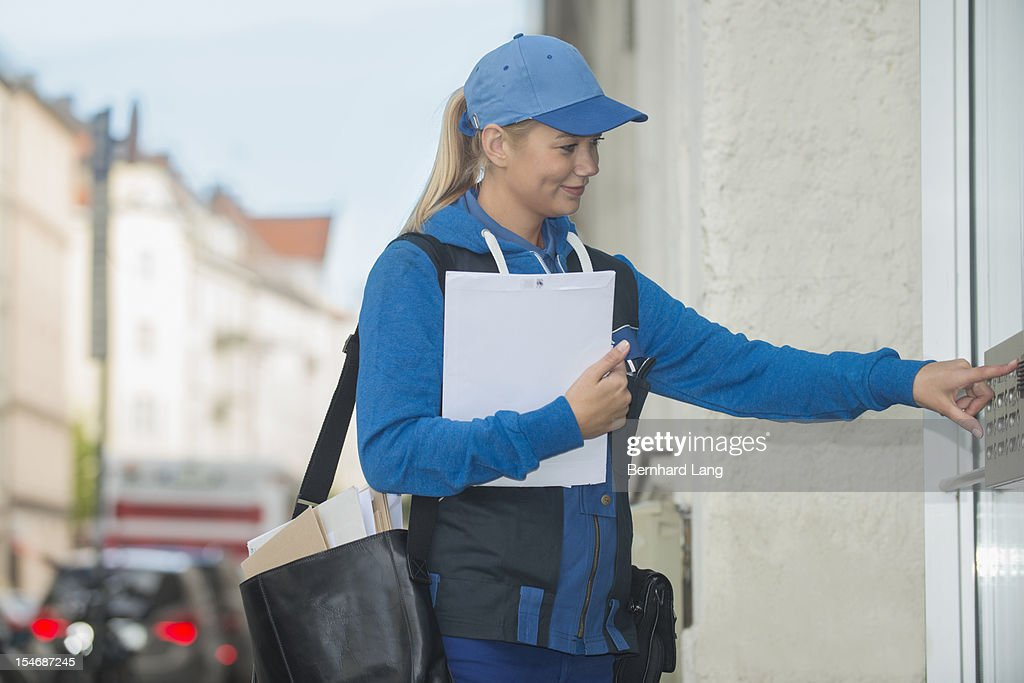 Female postal worker ringing bell : Photo