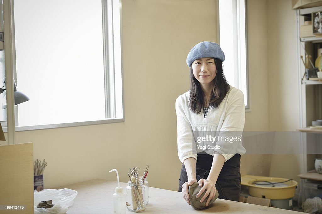 Female potter kneading clay in studio : Stock Photo