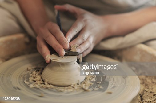 Female potter sharpening bowl?in studio