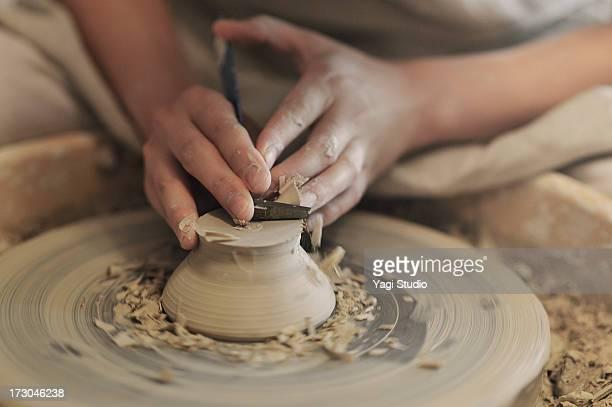 Female potter sharpening bowl?in studio