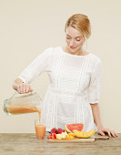 female pouring fruit smoothie into a glass