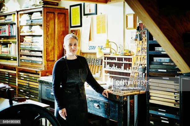 Female printer at workbench in letterpress studio