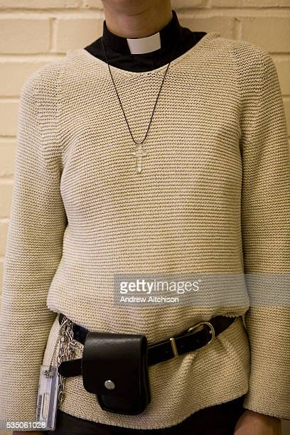 A female prison chaplain at HMP Downview Women's Prison stands with her Perspex cross dog collar security cards and utility belt displayed Prison...