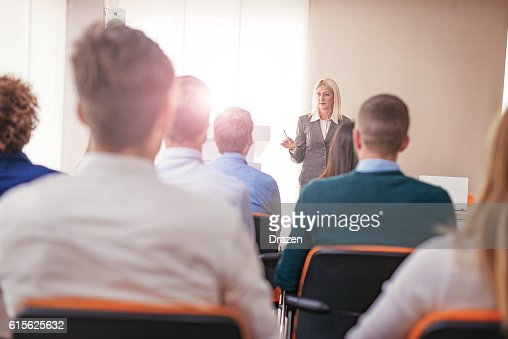 Female professor at faculty class, having discussion with students