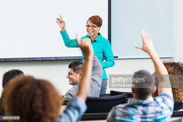 Female professor taking questions after lecture in college classroom