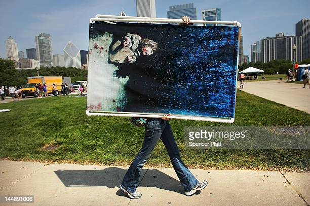 A female protester carries a painting that is the likeness of a photo made by Getty Images photographer Chris Hondros in Iraq in 2005 that shows an...