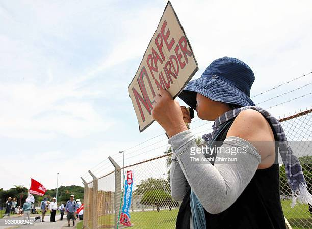 A female protester holding a banner 'No Rape Murder' demanding the withdrawal of US bases from Okinawa takes part in a rally in front of the US...