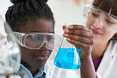 Female Pupil And Teacher Conducting Chemistry Experiment