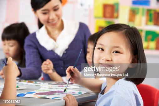 Female Pupil Enjoying Art Class In Chinese School Classroom : Foto de stock