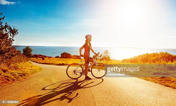 Female race cyclist stands next to bike near the sea