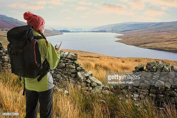 Female rambler checking GPS above lakeside