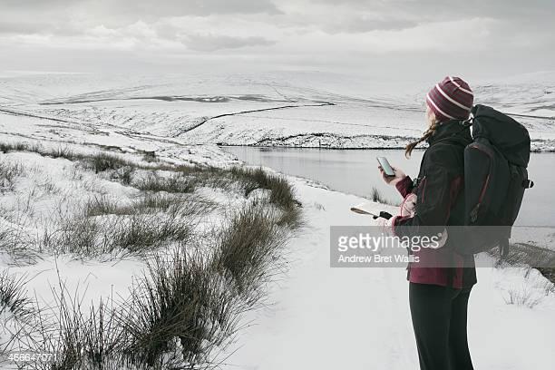 Female rambler checking GPS near winter lakeside