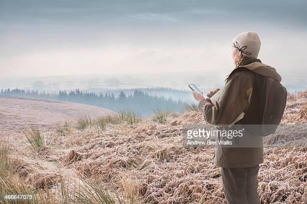 Female rambler checking GPS on winter moorland