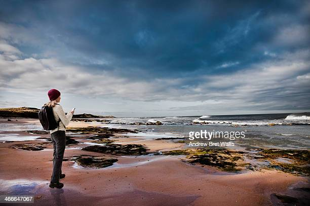 Female rambler using mobile on a deserted beach