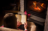 Female reading a book by the fireplace. Cozy winter lifestyle