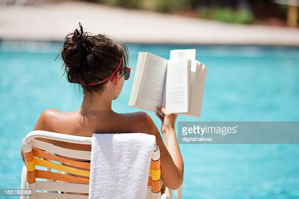 Female reading at the pool in the summer